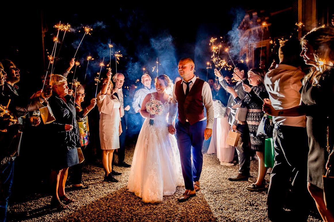 bruid en bruidegom worden uitgezwaaid door hun gasten