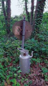Dans le bois, un seau est posé devant un tuyau d'arrivée d'eau.