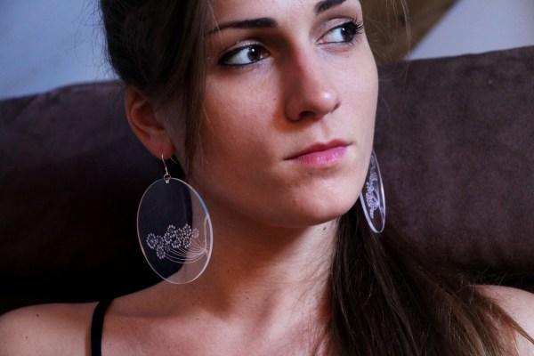 Fille avec des boucle d'oreille en plexiglas transparent gravé à la main de fleurs d'ombellifères