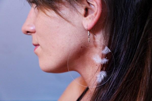 Fille avec des boucle d'oreille en plexiglas transparent gravé à la main de plumes