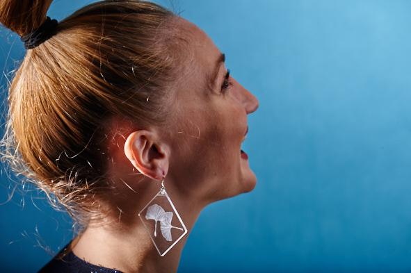Fille avec des boucle d'oreille en plexiglas transparent gravé à la main de feuille de Ginko