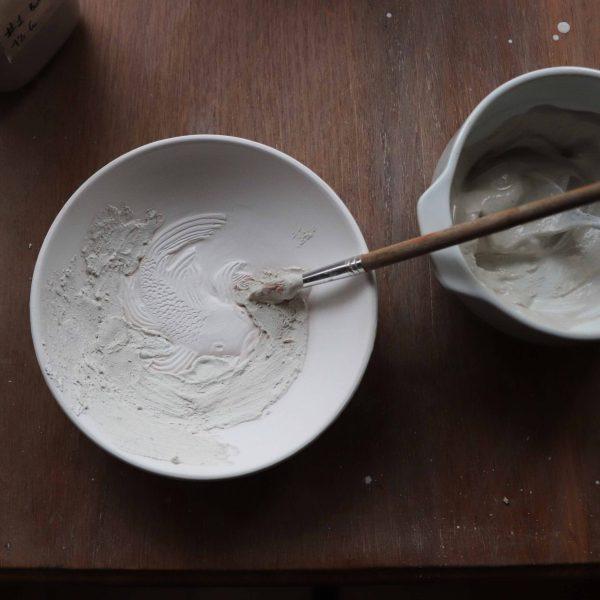 coupelle blanche en porcelaine avec un poisson gravé nageant et émaillage au pinceau
