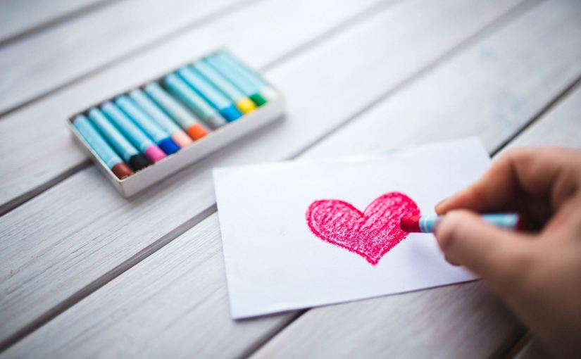 A hand draws a heart on an apology card using a pink crayon.