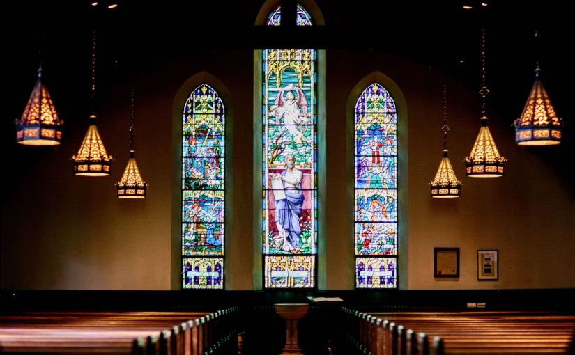A photograph of the inside of a church featuring stained-glass windows, dark wood pews, and hanging lights.