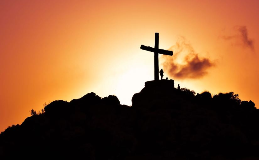 A silhouette of a hilltop cross at sunset.