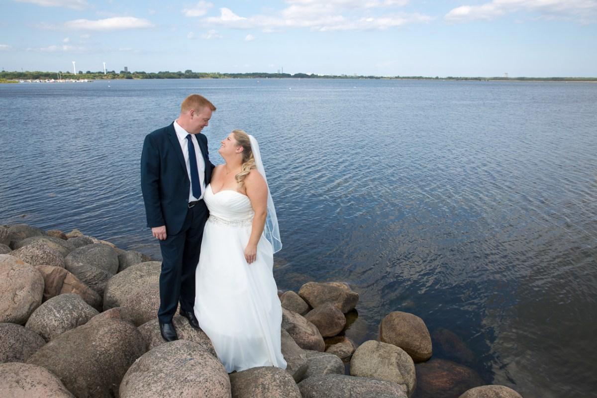 Brudepar på store sten ved vandet