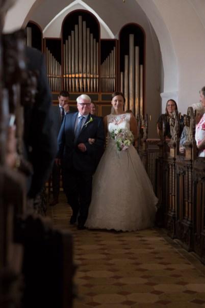 Det er bare et magisk øjeblik når bruden kommer ind i kirken. Gommen og gæsterne ser kjolen for første gang, og på dette billeder er lyset bare så fint.