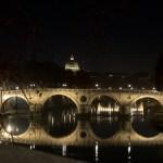 En bro lyst op i mørket, spejler sig i Tiberen, med Peterskirkens Kuppel i baggrunden