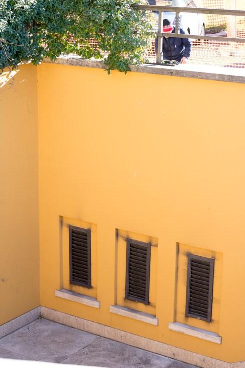 Tre små aflange vinduer i bunden af en gul væg