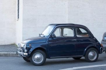 Blå minibil foran grå væg