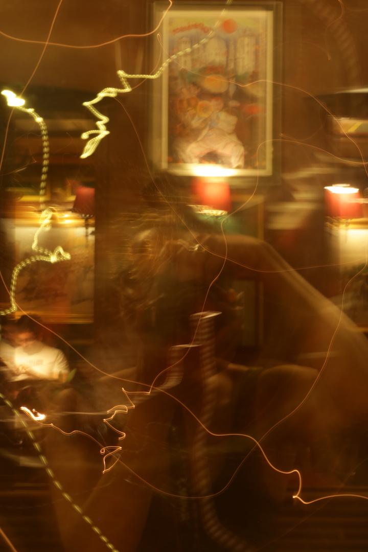 Spejlbillede af fotografen, omgivet af lys og billedrammer