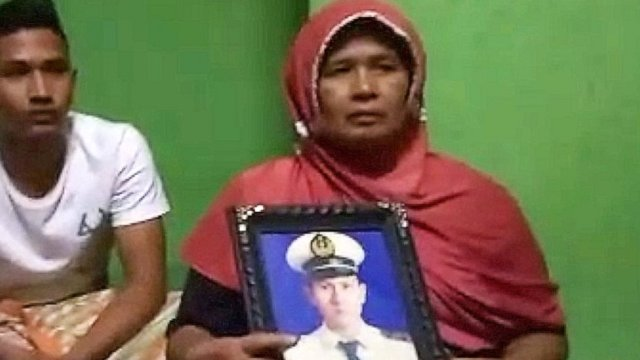 Afrida holding photo of her son at her home in Padang Sumatra