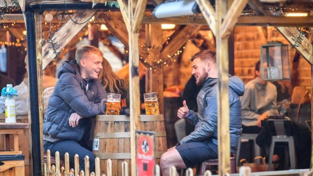 Two men drinking in a pub at a Christmas market