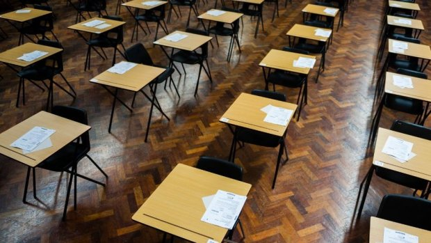 Rows of tables and chairs in a school exam hall