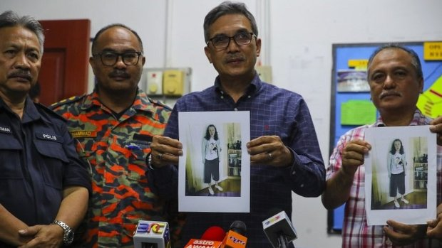 Police holding photos of Nora