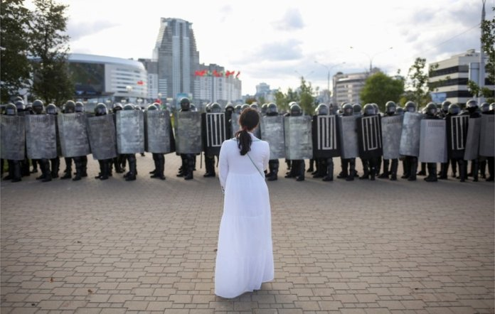 Woman in white facing line of riot police