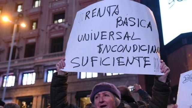 Persona en Madrid, España, con una pancarta pidiendo renta básica universal suficiente.