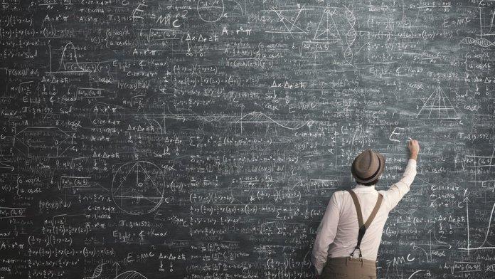 man writing formulas on a blackboard