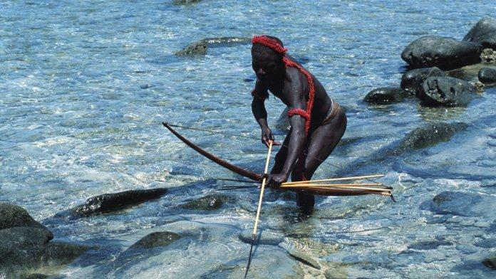 A Jarawa man standing in the water with a bow and arrow