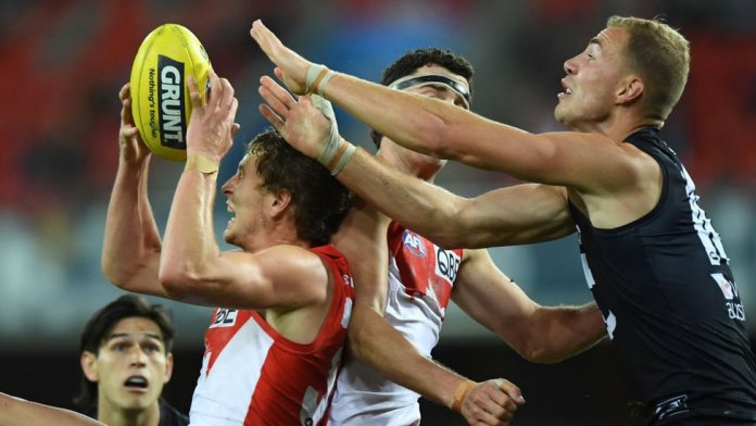An AFL player catches the ball amid a contest with other players