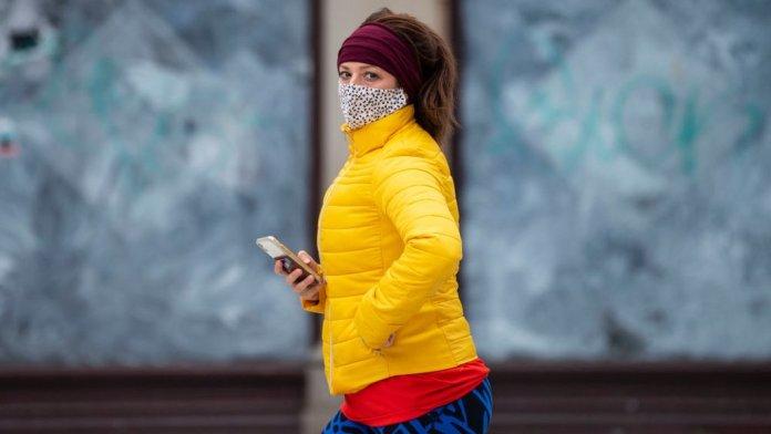 Woman walking past boarded up shop