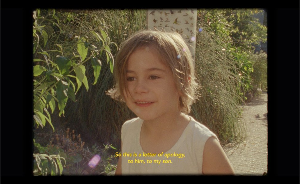 "A film still of a child with subtitles saying ""So this is a letter of apology, to him, to my son"""