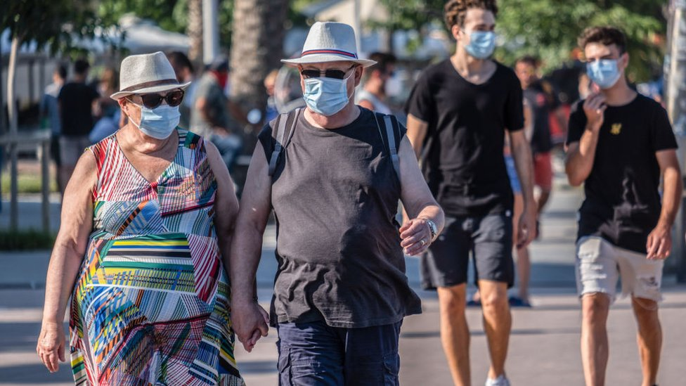 People with facemasks strolling in Barcelona.