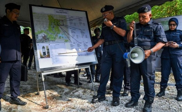 A Royal Malaysian Police officer conducts a briefing