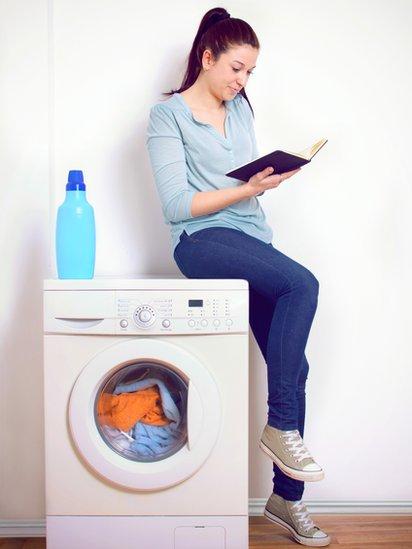 Una persona leyendo un libro apoyada en una lavadora.