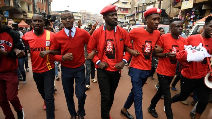 Musician turned politician Robert Kyagulanyi (C) is joined by other activists in Kampala on July 11, 2018 in Kampala during a demonstration to protest a controversial tax on the use of social media.