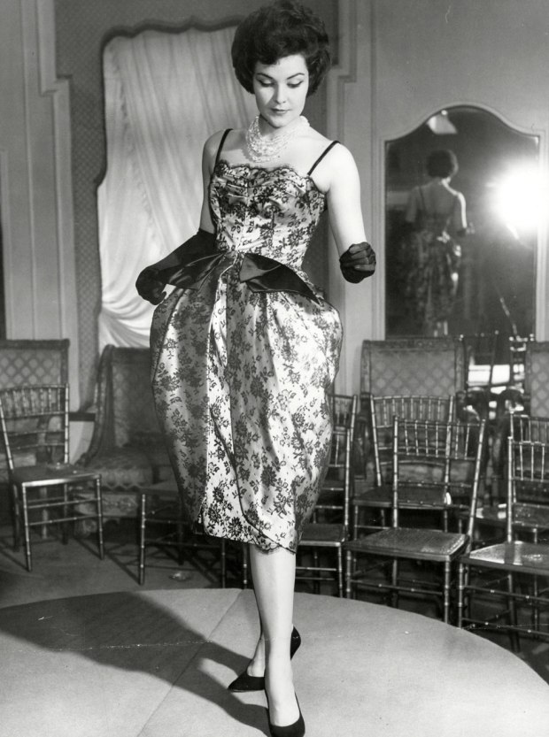 A model stands on a stage wearing a satin dress
