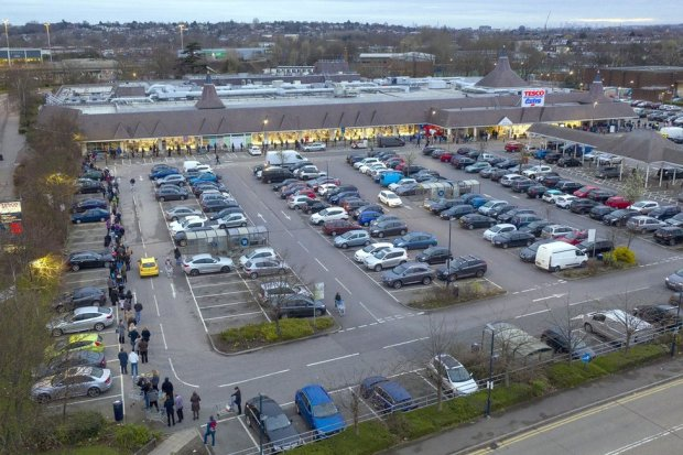 A large supermarket with a very long queue winding around the car park