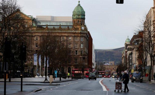 A woman walks across a deserted street in Belfast city centre