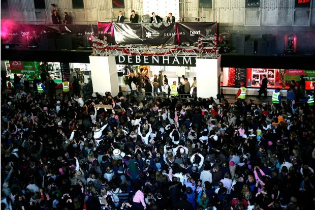 Westlife perform to a crowd outside of a Debenhams store