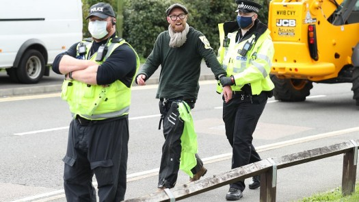 An Extinction Rebellion protester is led away by police from outside the Newsprinters printing works at Broxbourne, Hertfordshire