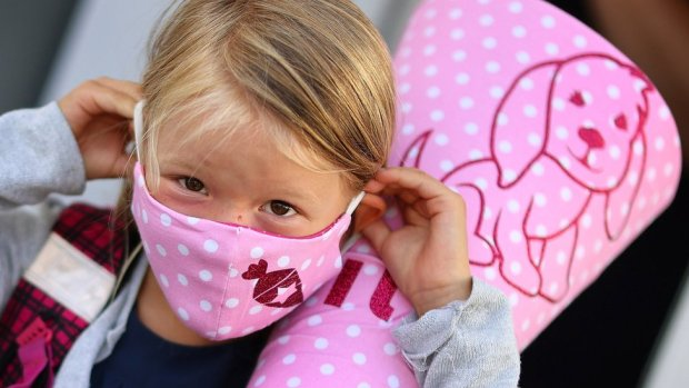 A six-year-old schoolgirl on her way to school in a facemask in Germany
