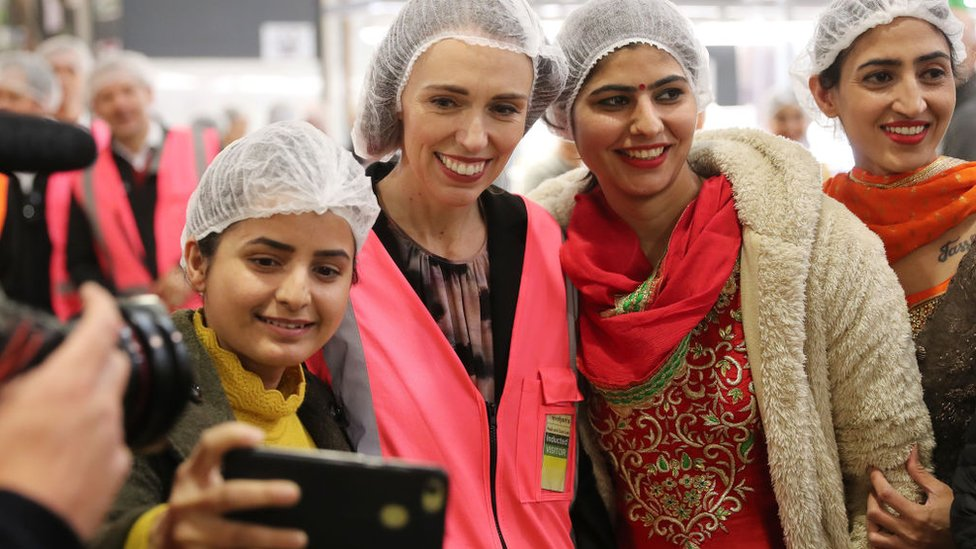 Prime Minister Jacinda Ardern poses with staff at a fruit packing plant.