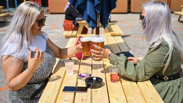 Two women with pints of beer sitting in a pub garden