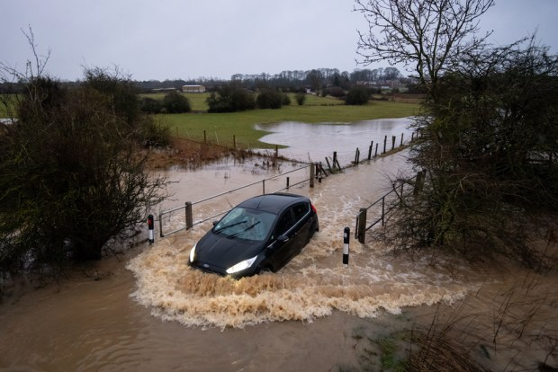 Cars pass through a flooded road in Leicester, on 14 January 2021
