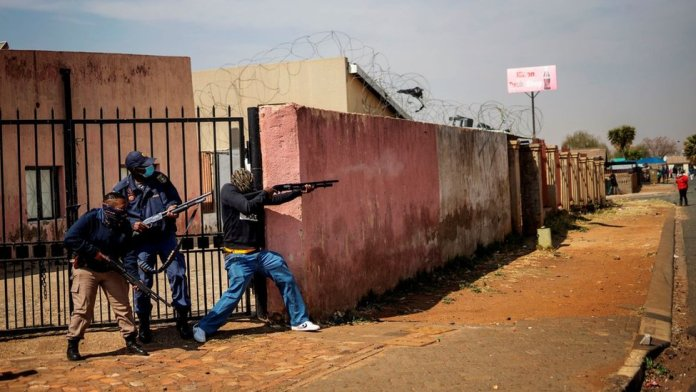 Members of the South African Police Service (SAPS) fire rubber bullets at residents in Eldorado Park, near Johannesburg, on August 27, 2020