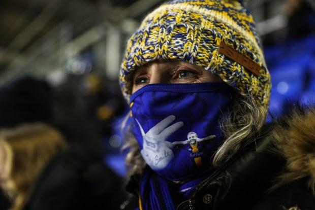 A Shrewsbury Town fan wears a face mask depicting striker Jason Cummings