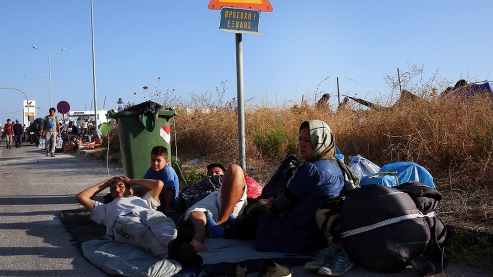 Migrants sit on a roadside near the site of the camp