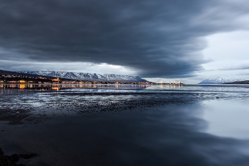 Clouds reflected over water with snow-capped mountains in the distance