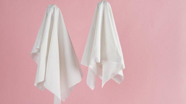 Dos sábanas como fantasmas en fondo rosa