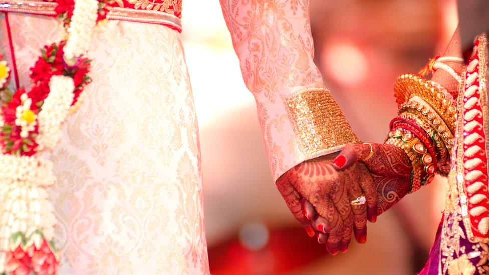 Marié tenant la main décorée au henné de la mariée (image générique)