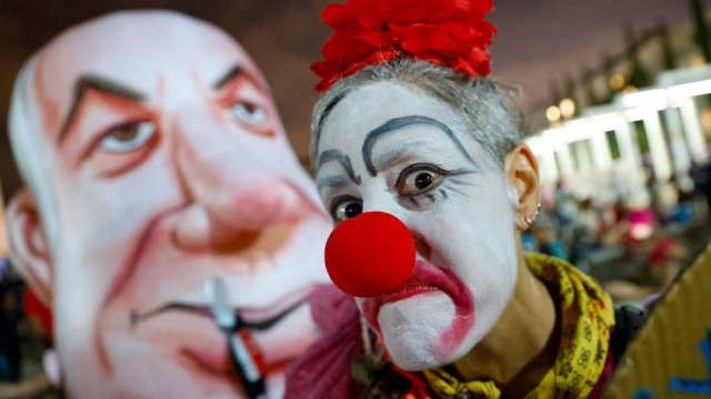 An Israeli woman wearing a clown outfit mocks Prime Minister Benjamin Netanyahu as she takes part in a demonstration against the government and an imminent and unprecedented second nationwide lockdown to tackle a spike in coronavirus, in Tel Aviv, on 17 September 2020.