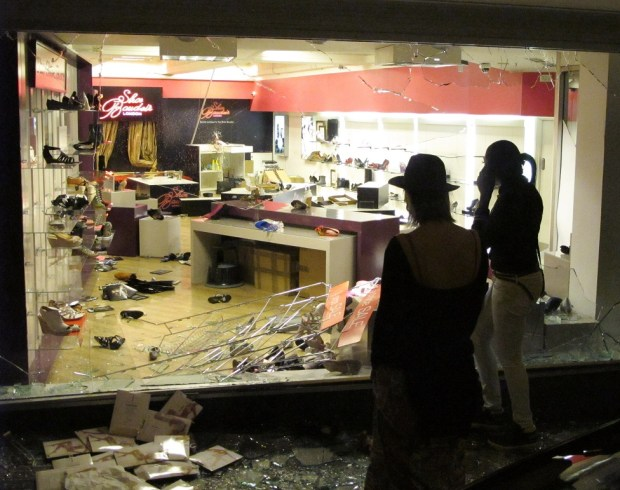 Two women look at a smashed store front