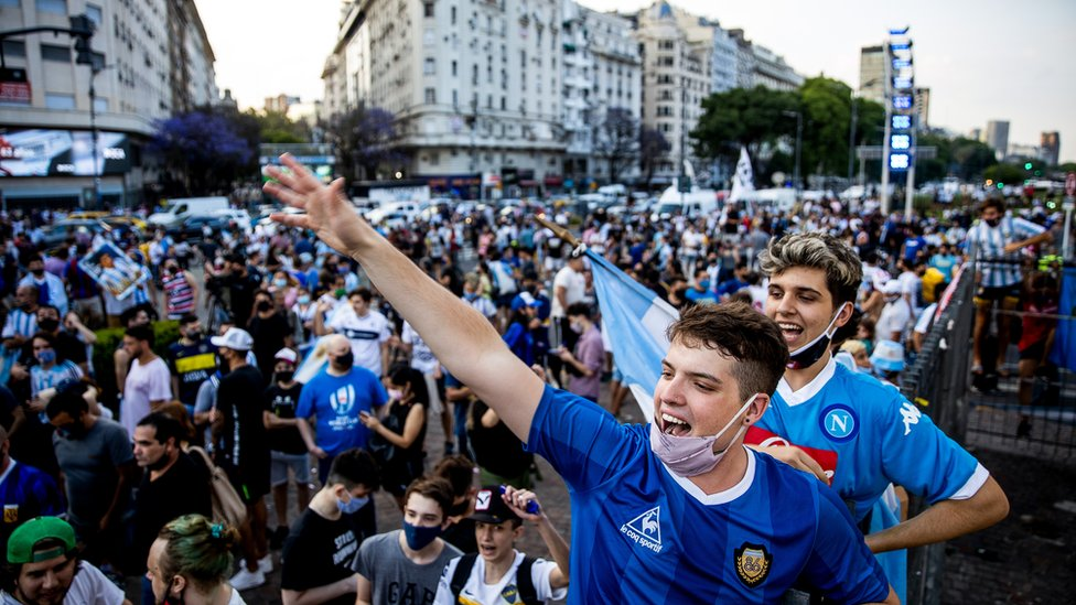 Fans cheer for Diego Maradona after the news of his death