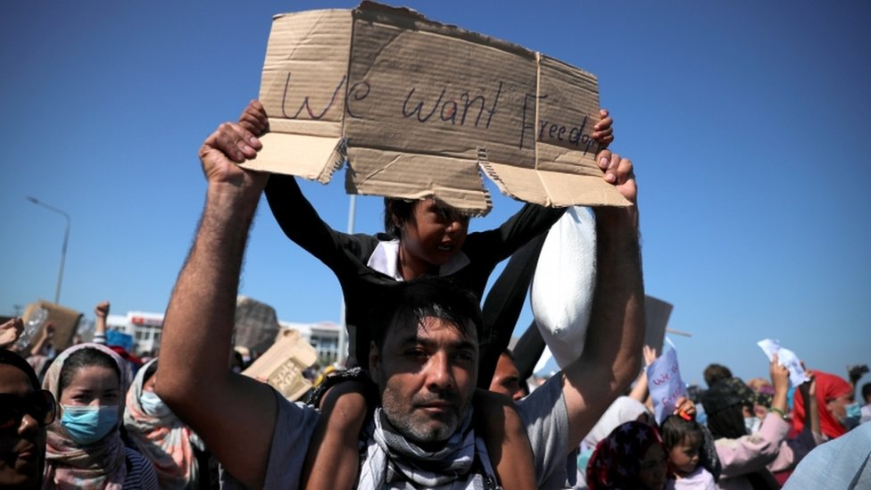 "A child on a man's shoulder holds a sign reading: ""We want freedom"""