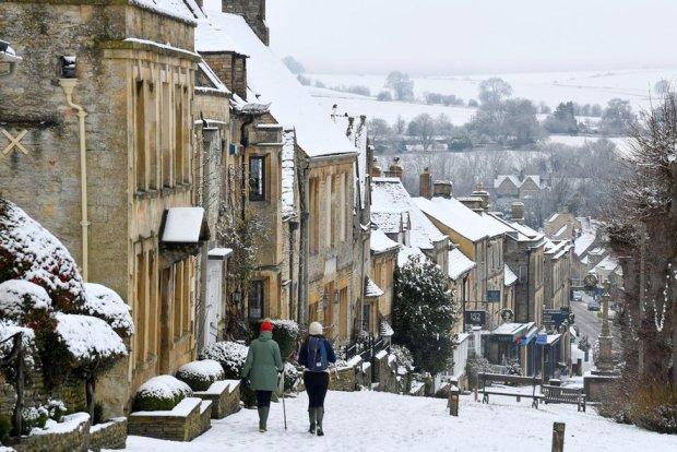 People walk through snow in Burford, 28 December 2020